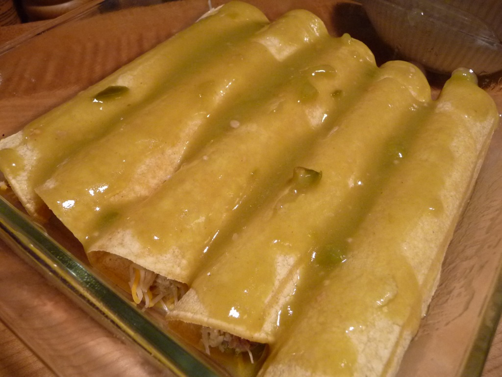 full baking dish of enchiladas with sauce on top